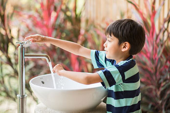 young lad washing his hands in a sink