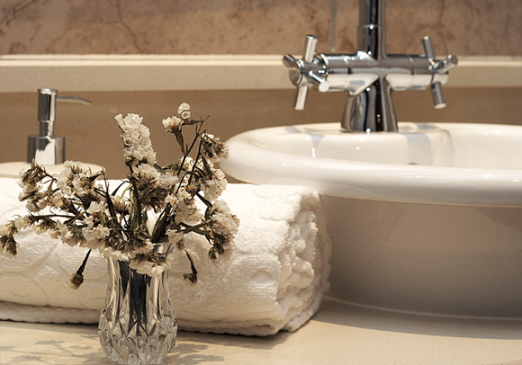 white, vessel-mounted sink basin and a clean, rolled-up towel