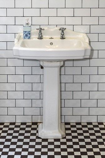 white porcelain sink with double tap atop a white pedestal